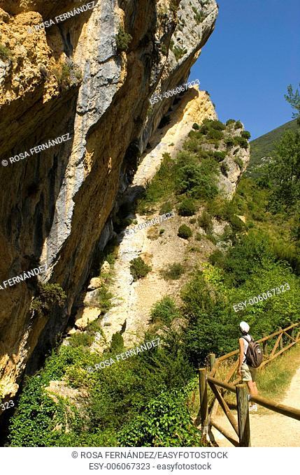 Tourist at the Puron River narrow pass, Ebro River basin, Obarenes Mountains, province of Burgos, Castilla y Leon, Spain