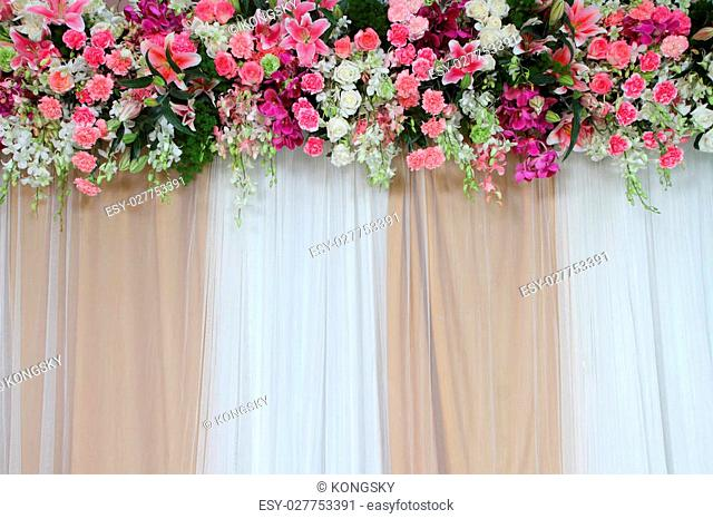 Colorful backdrop flowers with white and gold fabric arrangement ready for wedding ceremony