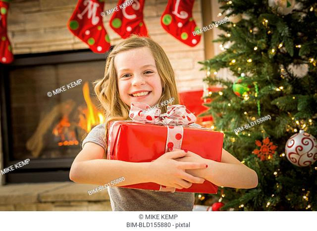 Caucasian girl hugging Christmas gift