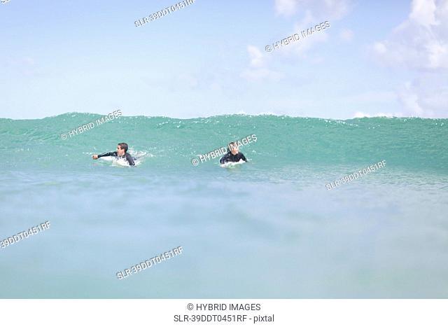 Teenage boys paddling with surfboard
