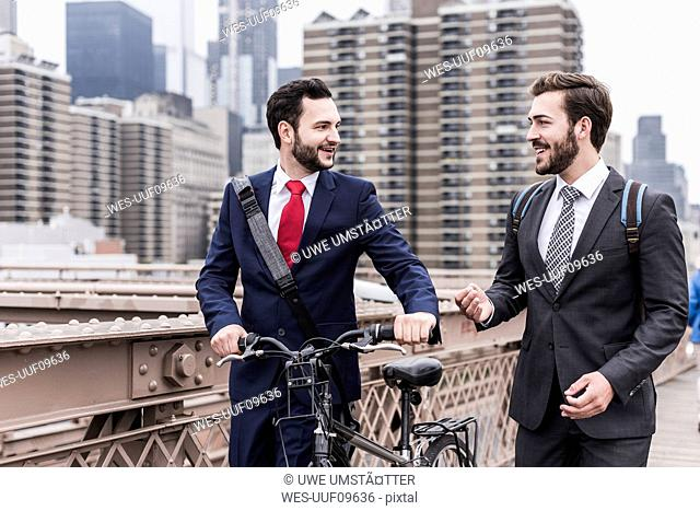 USA, New York City, two businessmen with bicycle on Brooklyn Bridge