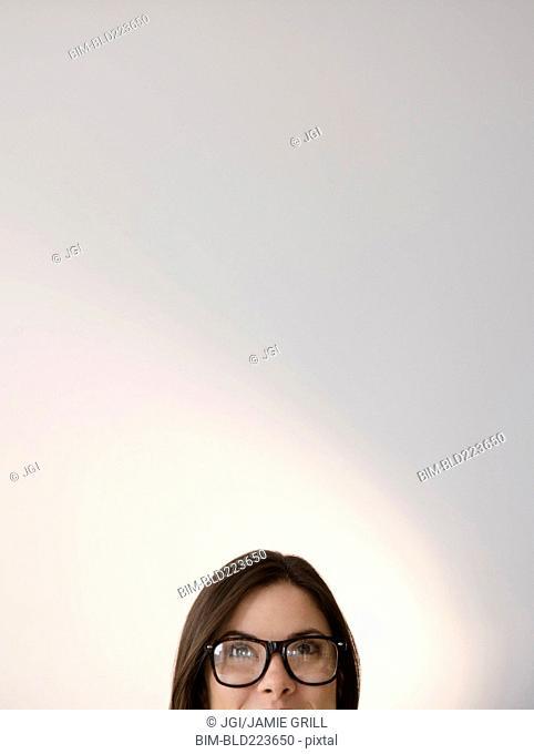 Face of Caucasian woman wearing eyeglasses looking up
