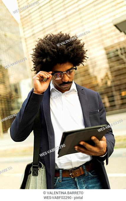 Spain, Barcelona, businessman in the city using tablet