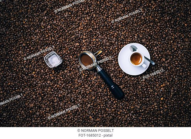 Directly above shot of espresso cup with filter and glass on roasted coffee beans