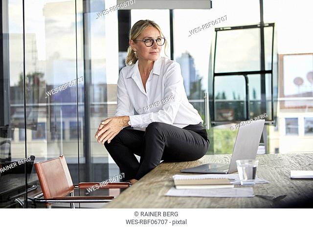 Successful businesswoman sitting on desk, contemplating