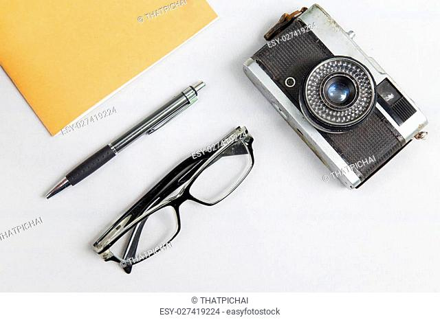 notebook with pen , glasses and camera on desk with white fabric background