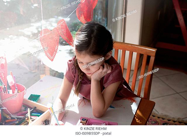 High angle view of girl sitting at table drawing