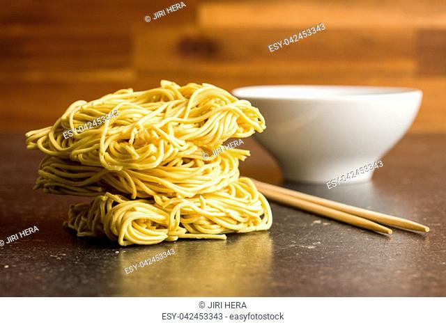 Uncooked instant chinese noodles on old kitchen table