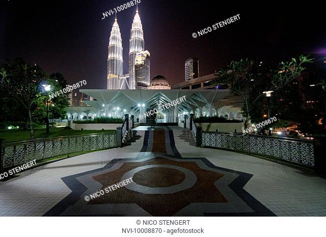 Masjid Asy Syakirin Mosque in front of Petronas Twin Towers illuminated at night, Kuala Lumpur, Malaysia, Southeast Asia, Asia