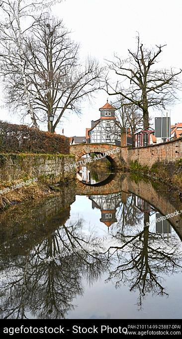 14 January 2021, Hessen, Bleichenbach: A half-timbered house and an old stone bridge are reflected in the stream of the same name in Bleichenbach in the...