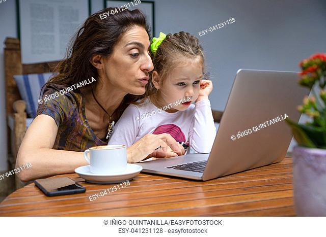 mother teaching her little daughter, girl four years old sitting on mother legs, surfing internet in laptop pc computer together
