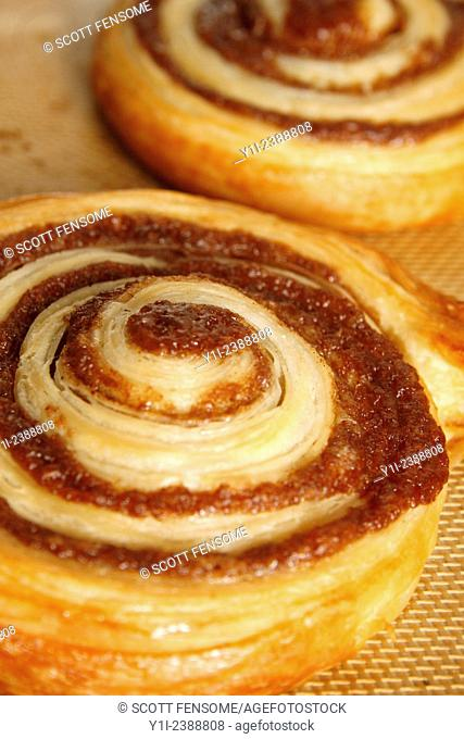 cinnamon swirls on baking mat fresh from the oven