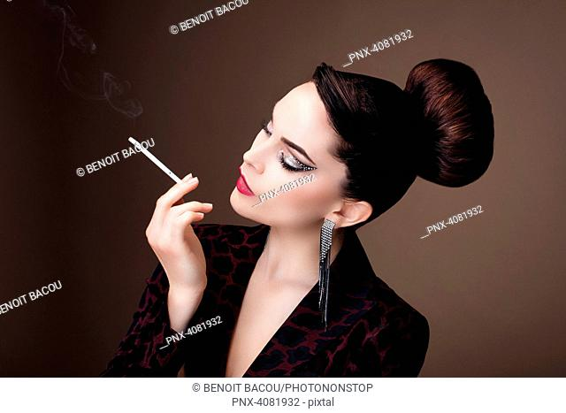 Portrait of a young woman in profile, smoking a fine cigarette
