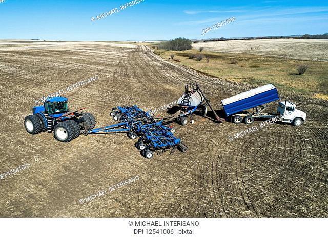 Aerial view of farmer filling an air seeder hopper with a truck in a field with blue sky in the background; Beiseker, Alberta, Canada