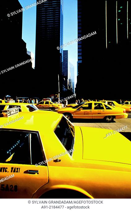 USA, New York Manhattan, cluster of yellow cabs against dark buildings in Fifth Avenue