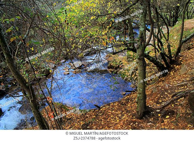 A large turkish blue puddle in the Aguilón river, in the middle of the trekking route to El Purgatorio waterfalls during a cold Autumn evening