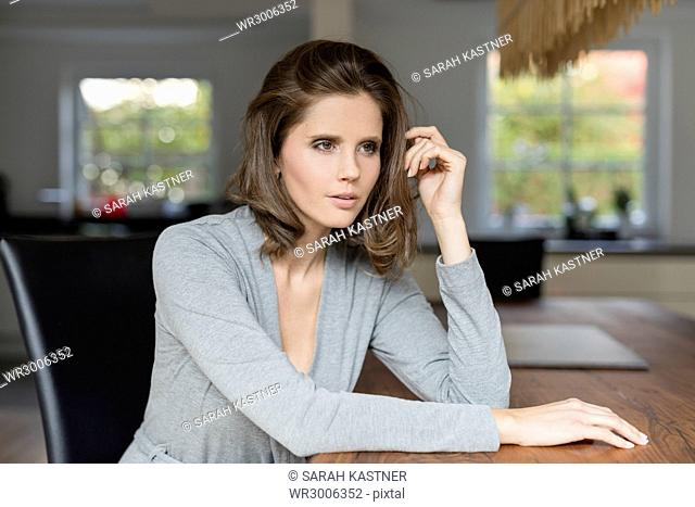 Young woman sitting at table in dining room