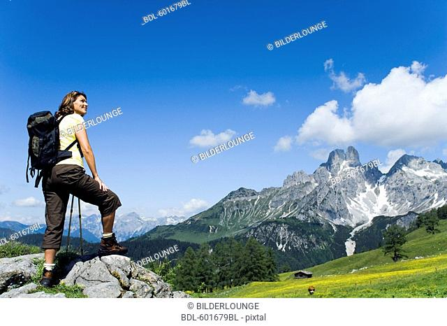 full body portrait of mature woman standing on rock in the mountains