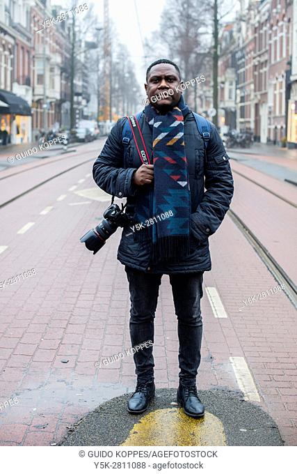 Amsterdam, Netherlands. Male photographer roaming the streets of the nation's capital, producing new photography for his portfolio