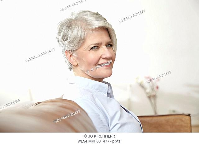 Portrait of smiling mature woman sitting on couch