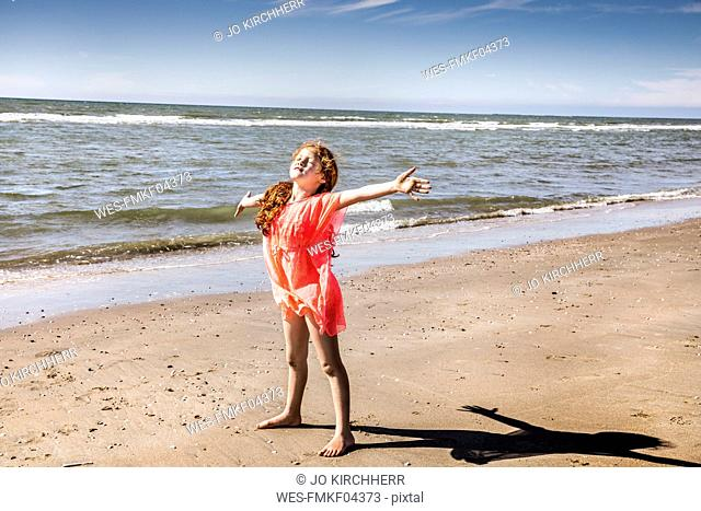 Netherlands, Zandvoort, girl standing on the beach with outstretched arms