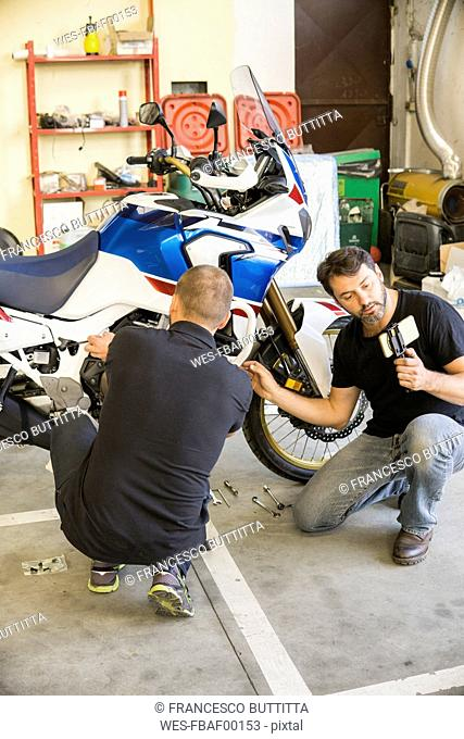 Mechanic working on motorcycle in workshop filmed by his partner