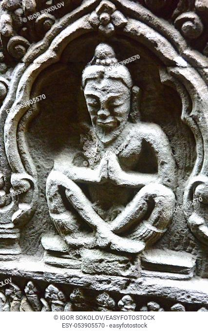 Stone bas-relief of a praying monk carved on the wall of the temple of Angkor Wat, Cambodia, Southeast Asia