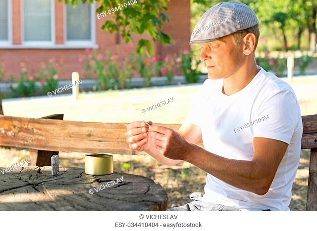Profile portrait of a Caucasian man rolling a cigarette while sitting at a rustic wooden table outdoors, in a summer day