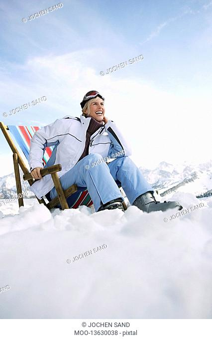 Female skier sitting on deckchair in mountains low angle view
