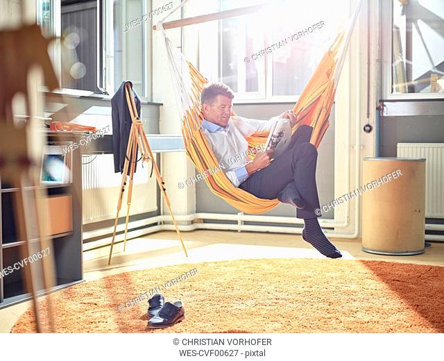 Mature businessman reading magazine in hammock at office