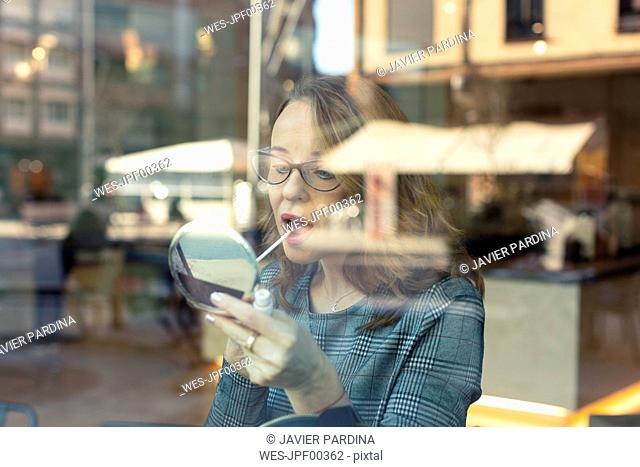 Mature woman with beauty mirror applying make-up in a cafe