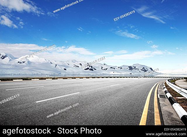 empty asphalt road with snow mountain