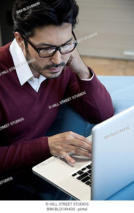 Hispanic man using laptop