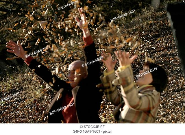 Man and woman throwing leaves in the air