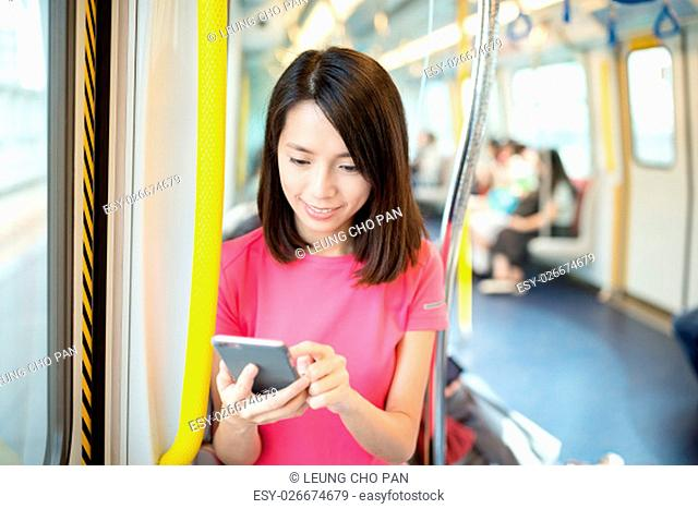 Woman use of mobile phone at train