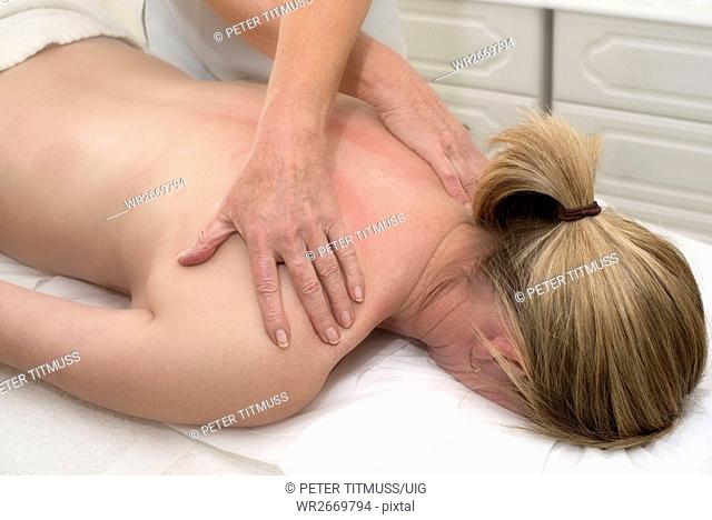Masseuse giving a massage to a female client