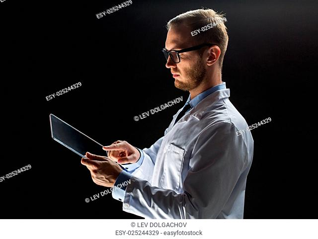 people, science, technology and medicine concept - close up of male doctor or scientist in white coat with tablet pc computer over black background