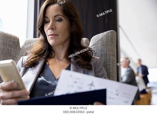 Serious businesswoman texting holding ticket in airport lounge