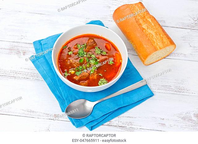 Lemongrass beef stew in a white bowl, with a piece of baguette, on a white background