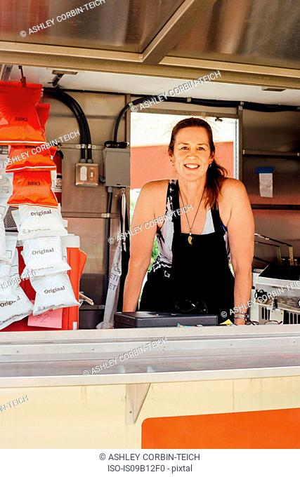 Portrait of woman at hatch of food stall trailer