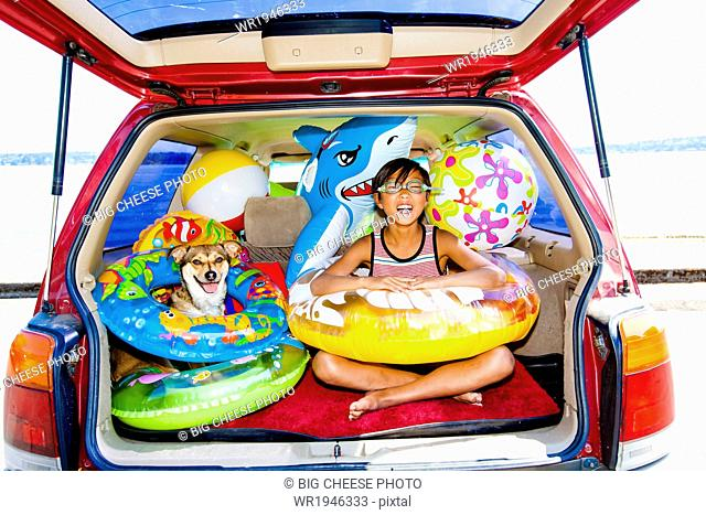 Child poses with his dog in the open trunk of a car full of beach toys and floaties