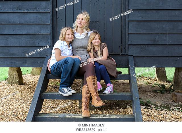 Caucasian mother and children hugging at shed