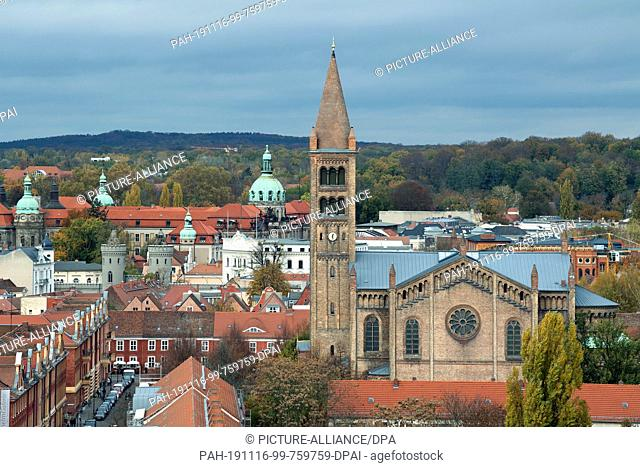 05 November 2019, Brandenburg, Potsdam: The church of St. Peter and Paul in front of the green domes of the town house and town hall on Friedrich-Ebert-Straße