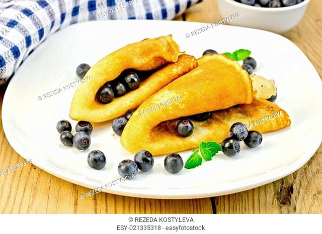 Pancakes with blueberries and napkin on board
