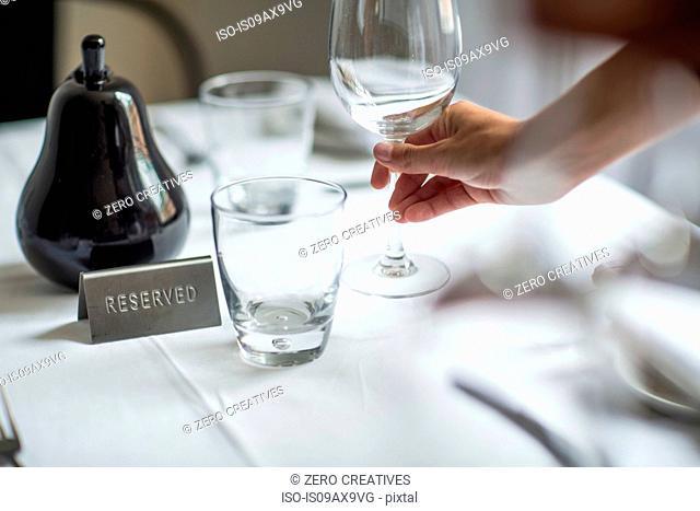 Waitress setting table in restaurant