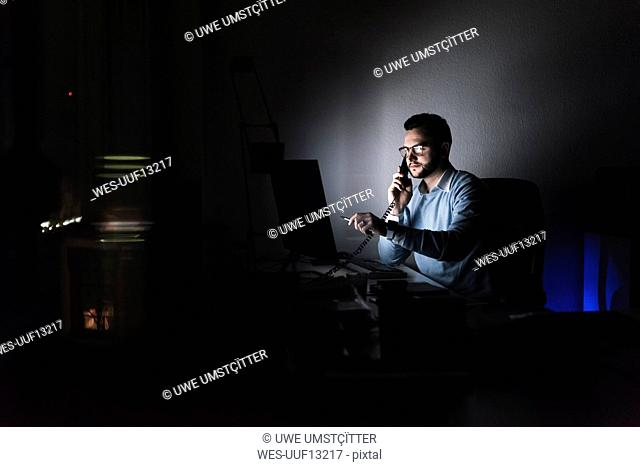 Businessman on the phone in office at night