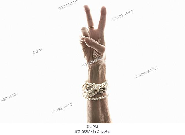 Studio shot of mature woman's hand making peace gesture