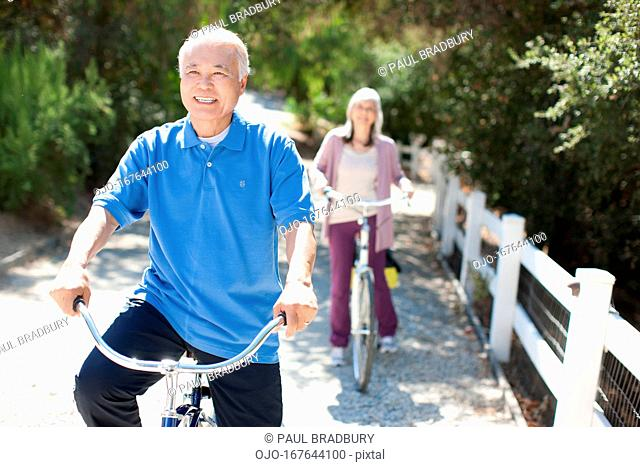 Smiling older couple riding bicycles
