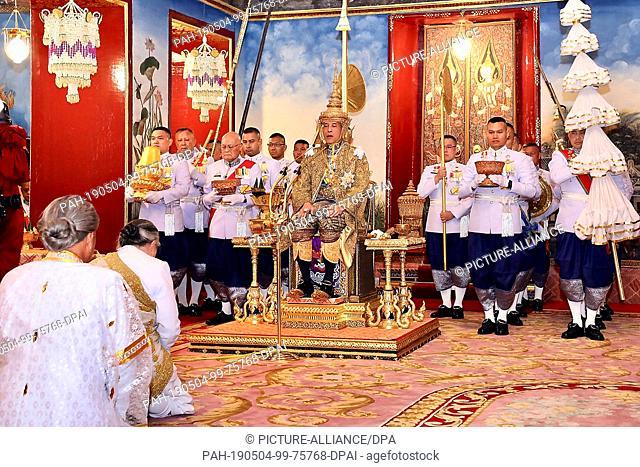 HANDOUT - 04 May 2019, Thailand, Bangkok: Maha Vajiralongkorn (M), King of Thailand, sits on the throne before diplomats and dignitaries at his coronation
