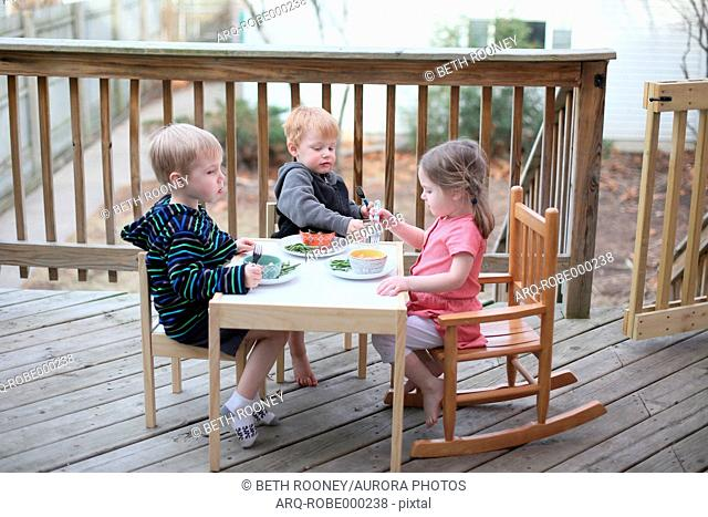 Three Kids Eating Outside In Early Spring